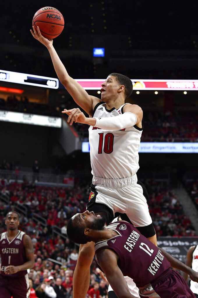 Louisville guard Samuell Williamson (10) goes in for a layup over the defense of Eastern Kentucky guard Ty Taylor II (12) during the second half of an NCAA college basketball game in Louisville, Ky., Saturday, Dec. 14, 2019. Louisville won 99-67. (AP Photo/Timothy D. Easley)