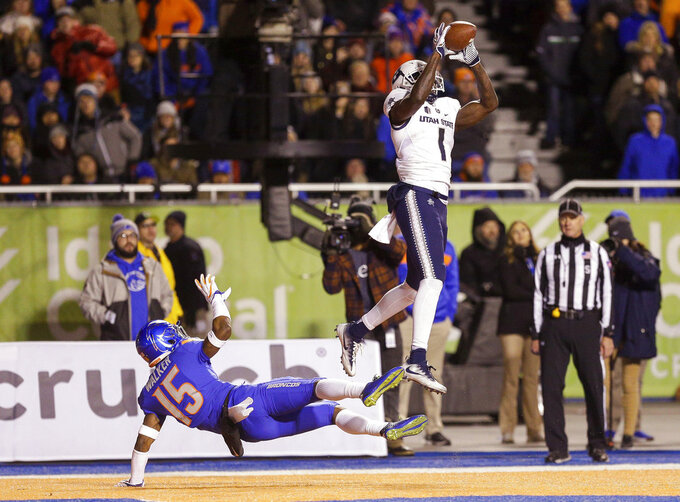 Utah State wide receiver Ron'quavion Tarver (1) catches a touchdown pass over Boise State cornerback Jalen Walker (15) during the first half of an NCAA college football game Saturday, Nov. 24, 2018, in Boise, Idaho. (AP Photo/Steve Conner)