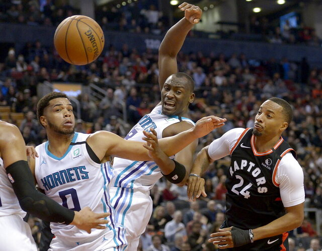 Toronto Raptors guard Norman Powell (24) loses the ball to Charlotte Hornets forward Miles Bridges (0) as Hornets center Bismack Biyombo (8) looks on during second-half NBA basketball game action in Toronto, Friday, Feb. 28, 2020. (Nathan Denette/The Canadian Press via AP)