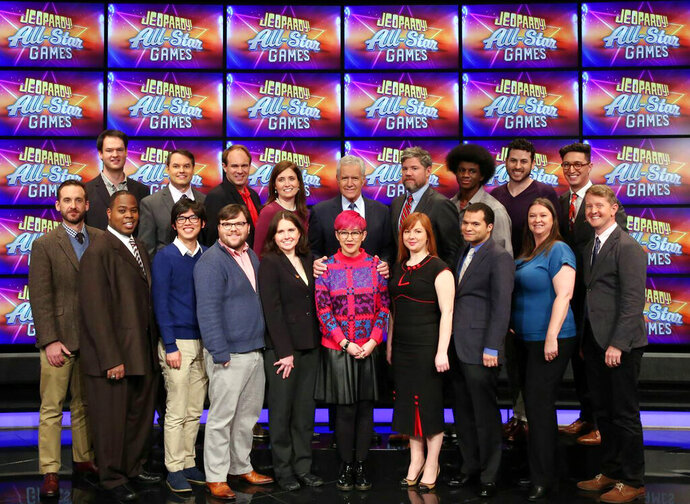 This image released by Jeopardy Productions, Inc. shows, front row from left, Brad Rutter, Colby Burnett, Alan Lin, Seth Wilson, Larissa Kelly, Monica Thieu, Pam Mueller, Matt Jackson, Jennifer Giles and Ken Jennings, back row from left, Ben Ingram,  Roger Craig, David Madden, Julia Collins, host Alex Trebek, Austin Rogers, Leonard Cooper, Alex Jacob and Buzzy Cohen on the set of the game show
