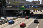 Traffic moves under a homeless encampment that sits on the Main St. overpass of the 101 freeway during the coronavirus outbreak, Thursday, May 21, 2020, in downtown Los Angeles. (AP Photo/Mark J. Terrill)
