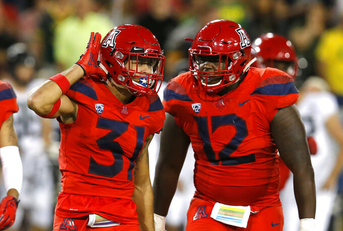 Arizona safety Tristan Cooper (31) celebrates with JB Brown after defeating Oregon 44-15 during an NCAA college football game, Saturday, Oct. 27, 2018, in Tucson, Ariz. Arizona defeated Oregon 44-15. (AP Photo/Rick Scuteri)