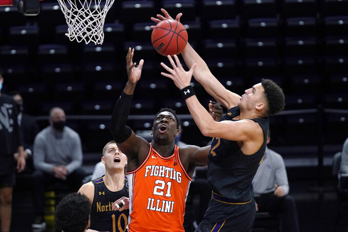 Northwestern forward Pete Nance, right, reaches for a rebound above Illinois center Kofi Cockburn during the first half of an NCAA college basketball game in Evanston, Ill., Thursday, Jan. 7, 2021. (AP Photo/Nam Y. Huh)