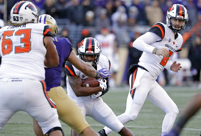 Oregon State quarterback Jake Luton, right, watches after handing off the ball to Artavis Pierce in the first half of an NCAA college football game against Washington, Saturday, Nov. 17, 2018, in Seattle. (AP Photo/Elaine Thompson)
