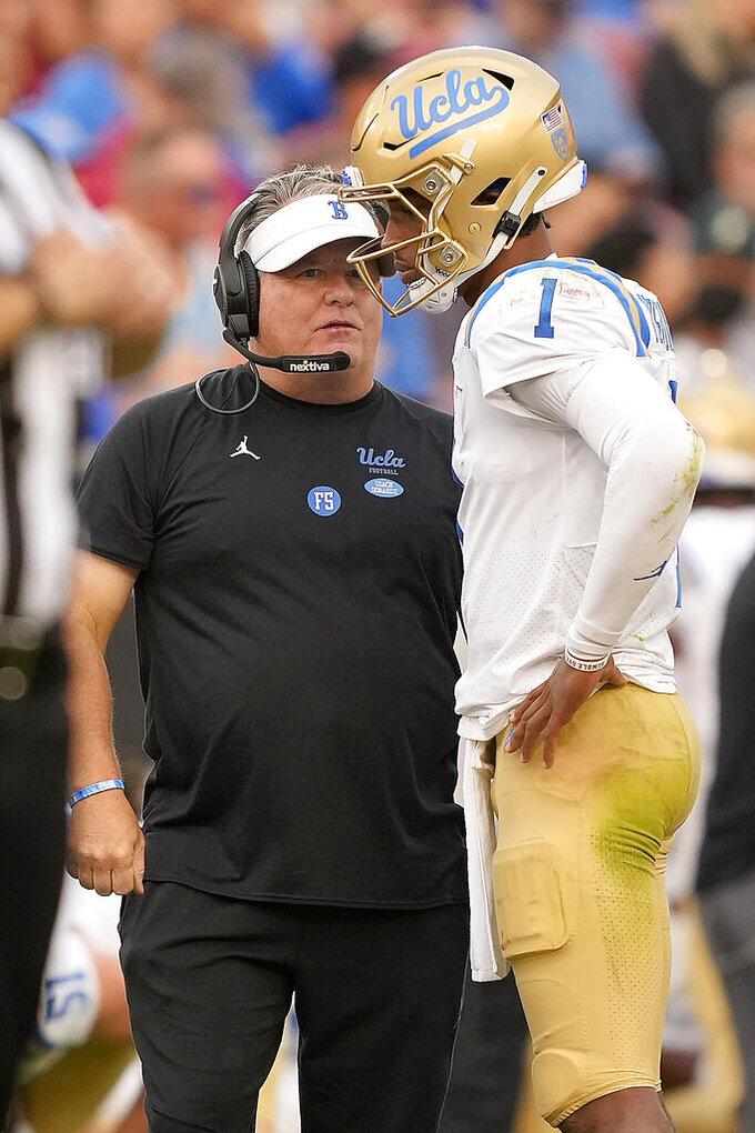 UCLA quarterback Dorian Thompson-Robinson (1) talks with head coach Chip Kelly, left, during a time out against Stanford during the second half of an NCAA college football game Saturday, Sept. 25, 2021, in Stanford, Calif. (AP Photo/Tony Avelar)