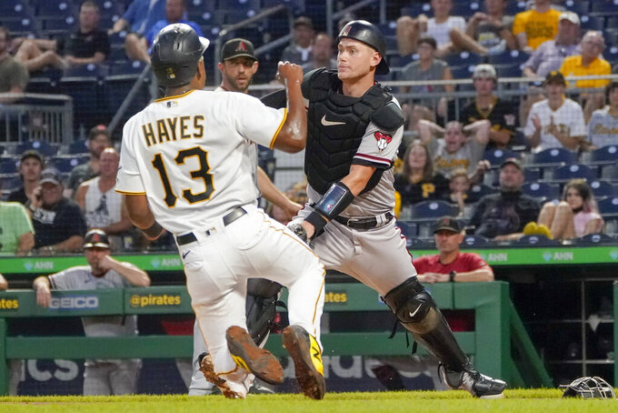 Arizona Diamondbacks catcher Carson Kelly, right, awaits the throw as Pittsburgh Pirates' Ke'Bryan Hayes (13) scores on a sacrifice fly by Bryan Reynolds during the third inning of a baseball game Tuesday, Aug. 24, 2021, in Pittsburgh. (AP Photo/Keith Srakocic)
