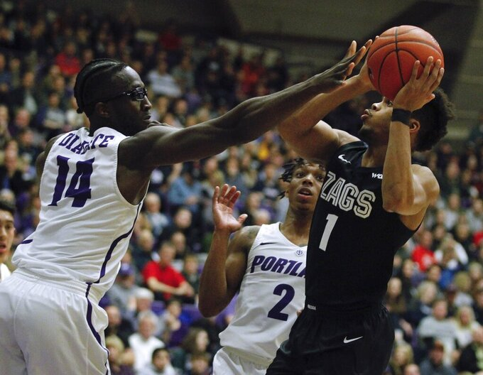 Portland forward Tahirou Diabate, left, and Portland guard JoJo Walker, center, defend against Gonzaga guard Admon Gilder, right during the first half of an NCAA college basketball game in Portland, Ore., Thursday, Jan. 2, 2020. (AP Photo/Steve Dipaola)