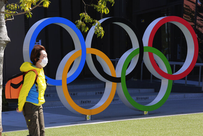 A woman walks past the Olympic rings in Tokyo, Wednesday, March 10, 2021. (AP Photo/Koji Sasahara)