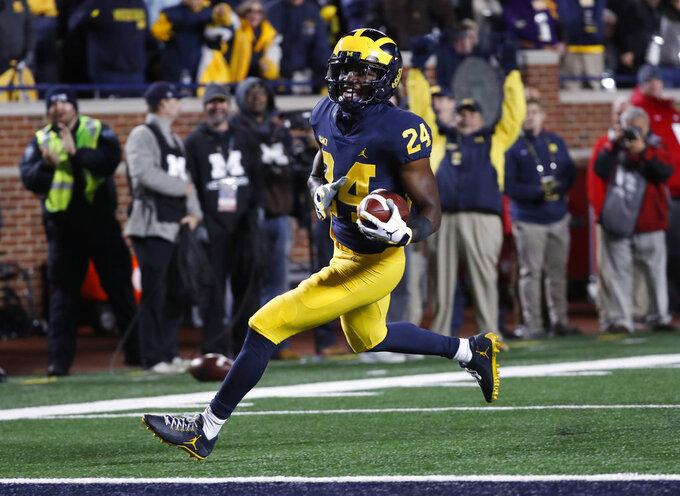 Michigan defensive back Lavert Hill returns an interception for a 21-yard touchdown during the second half of an NCAA college football game against Wisconsin in Ann Arbor, Mich., Saturday, Oct. 13, 2018. (AP Photo/Paul Sancya)