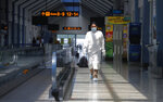 A Sri Lankan airport worker in protective suit walks inside a terminal at the Katunayake International Airport in Colombo, Sri Lanka, Wednesday, Jan. 20, 2021. Sri Lanka's tourism minister said that the airports in the country will be reopened for tourists according to health guidelines from Jan.21. (AP Photo/Eranga Jayawardena)
