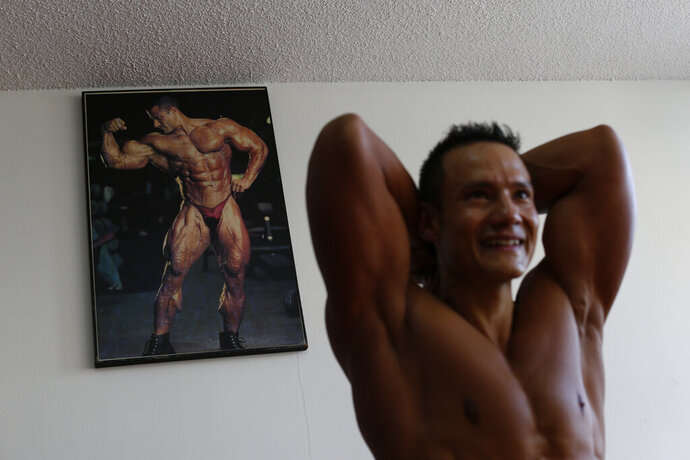 In this June 6, 2019 photo, Carlos Suarez practices his bodybuilding poses as part of his daily training regimen ahead of the Pan Am Games, at the neighborhood gym owned by his parents in Toluca, Mexico. Suarez and female fitness competitor Xyomara Valdivia will become the first Mexicans to represent their country in bodybuilding at the Pan Am Games, with this year marking the first time the discipline has been included as an official sport. (AP Photo/Rebecca Blackwell)