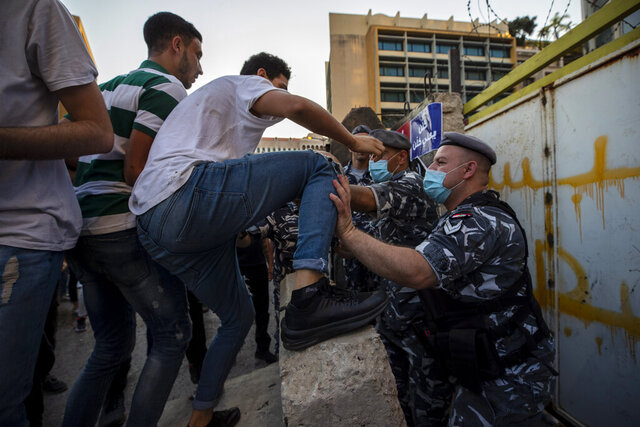 Anti-government protesters scuffle with Lebanese policemen after they removed a part of a concrete wall that was installed by security forces to prevent them from reaching the government palace in Beirut, Lebanon, Thursday, July 2, 2020. Major retailers in Lebanon announced Thursday they will temporarily close in the face of an increasingly volatile currency market and their inability to set prices while the local currency tumbles before the dollar. (AP Photo/Hassan Ammar)
