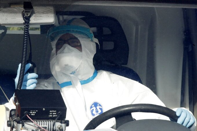A paramedic wearing protective gear drives an ambulance in central Athens, Tuesday, Oct. 20, 2020. Greece has been experiencing a resurgence of the coronavirus, with the number of new daily cases, most in the Greek capital, often topping 400, and both deaths and the number of those in intensive care units rising. (AP Photo/Thanassis Stavrakis)