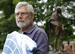 In this Wednesday, Aug. 21, 2019 photo, Lewis Randa, of Duxbury, Mass., holds a United Nations flag while standing near a bronze statue of Indian independence leader Mahatma Gandhi, behind right, at the Pacifist Memorial, in Sherborn, Mass. Randa says in mid-August of 2019 he removed the flag because owners of a condo association, who now own the land on which the Pacifist Memorial is located, argue it violates their property agreement. Randa founded the memorial in 1994. (AP Photo/Steven Senne)