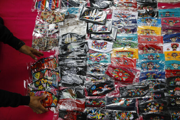 FILE - In this Aug. 17, 2020 file photo, Luis Fuentes, 45, from Ecuador, gathers up face masks decorated with traditional Mexican designs, as he puts away his wares as it begins to rain, on Insurgentes Avenue in Mexico City. According to a report released the third week of April, by the University of California, San Francisco, Mexico would have had a significantly lower COVID-19 death toll if it had reacted as well as the average government. (AP Photo/Rebecca Blackwell, File)