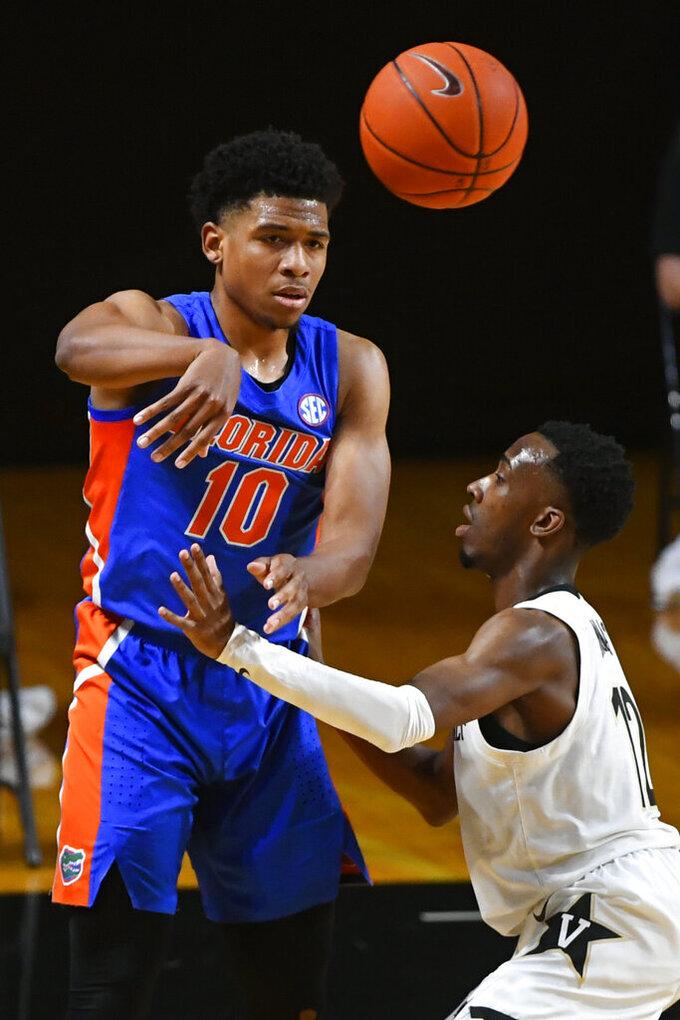 Florida guard Noah Locke (10) passes the ball as Vanderbilt guard Trey Thomas defends during the first half of an NCAA college basketball game Wednesday, Dec. 30, 2020, in Nashville, Tenn. (AP Photo/John Amis)