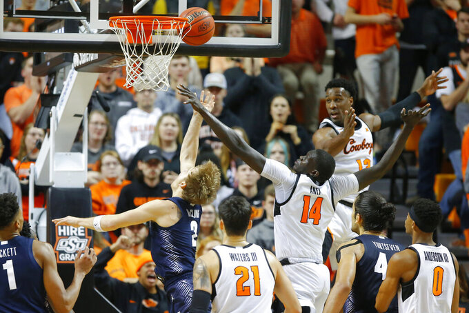 Georgetown's Mac McClung (2) is fouled by Oklahoma State's Yor Anei (14) as he makes a basket during an NCAA college basketball game in Stillwater, Okla., Wednesday, Dec. 4, 2019. (Bryan Terry/The Oklahoman via AP)