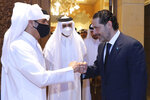In this photo released by Lebanon's official government photographer Dalati Nohra, Lebanese Prime Minister-Designate Saad Hariri, right, greets with a fist bump Qatar's Deputy Prime Minister and Foreign Minister Sheikh Mohammed bin Abdulrahman bin Jassim Al-Thani, as he welcomes him at his house, in Beirut, Lebanon, Tuesday, July 6, 2021. Qatar's Foreign Minster is in Beirut for one day visit to meet with Lebanese officials and the Lebanese Army Commander Gen. Joseph Aoun. (Lebanon Government/Dalati Nohra via AP)