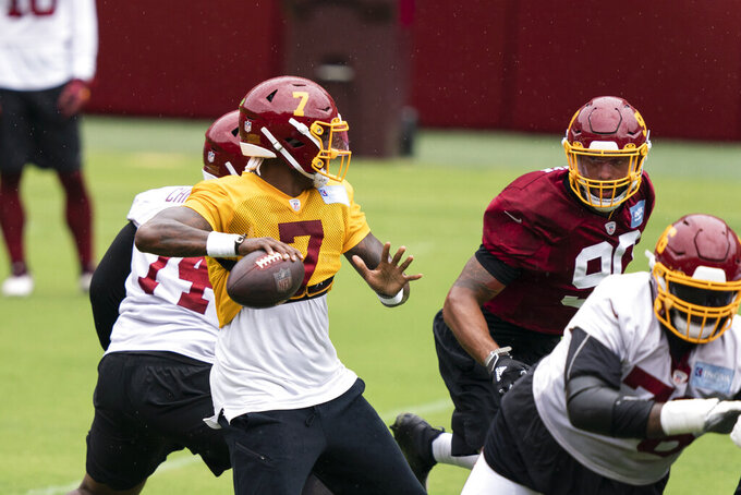 Washington quarterback Dwayne Haskins Jr. (7) looks to pass with defensive end Montez Sweat (90) nearby during an NFL football practice at FedEx Field, Monday, Aug. 31, 2020, in Washington. (AP Photo/Alex Brandon)