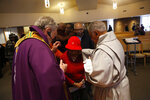 In this Sunday, Dec. 1, 2019 photo, Rev. Philip Schmitter anoints a parishioner after Mass at Christ the King Catholic Church in Flint, Mich. Schmitter, 74, has served the beleaguered city of Flint for 50 years, often inserting himself into social justice issues, including those related to race, environment and poverty. He says it can be stressful, but he loves what he does and feels particularly called to serve African Americans, whether Catholic or not. (AP Photo/Martha Irvine)