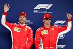 Ferrari driver Sebastian Vettel of Germany, left, waves with his teammate Kimi Raikkonen of Finland after taking pole position for the Chinese Formula One Grand Prix at the Shanghai International Circuit in Shanghai, Saturday, April 14, 2018. Raikkonen finished second. (AP Photo/Andy Wong)