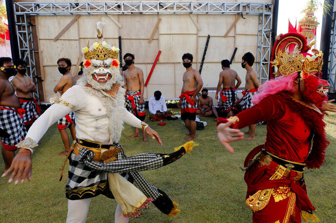Traditional dancers wear costumes as they prepare their performance in a parade in Bali, Indonesia on Thursday, July 30, 2020. Indonesia's resort island of Bali will reopen for domestic tourists on Friday after months of virus lockdown. (AP Photo/Firdia Lisnawati)