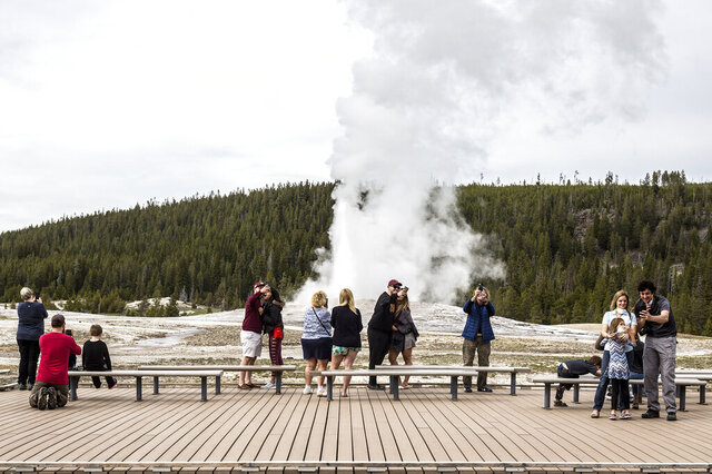 In this Monday, May 18, 2020 photo, visitors watch as Old Faithful erupts on the day the park partially reopened after a two-month shutdown due to the coronavirus pandemic, at Yellowstone National Park, Wyo. Officials at Yellowstone and other national parks plan to let tourists mostly police themselves and not intervene much to enforce social distancing. (Ryan Dorgan/Jackson Hole News & Guide via AP)