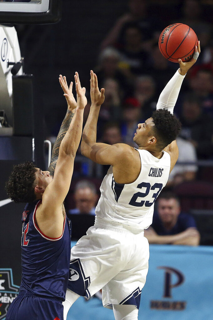 BYU's Yoeli Childs shoots as Saint Mary's Dan Fotu defends during the first half of an NCAA college basketball game in the West Coast Conference tournament, Monday, March 9, 2020, in Las Vegas. (AP Photo/Isaac Brekken)