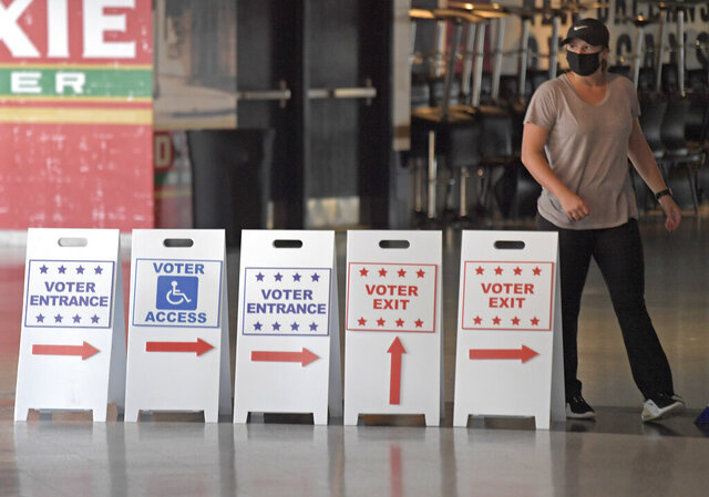 A member of the Louisiana Secretary of State's elections office, Stephanie Pourciau, helps build signs at the Smoothie King Center in New Orleans, La. Thursday, Oct. 15, 2020. Early voting will run from Oct. 16 to Oct. 27 - except on Sundays - from 8 a.m. to 7 p.m. at the arena and four other locations in New Orleans (Max Becherer/The Times-Picayune/The New Orleans Advocate via AP)