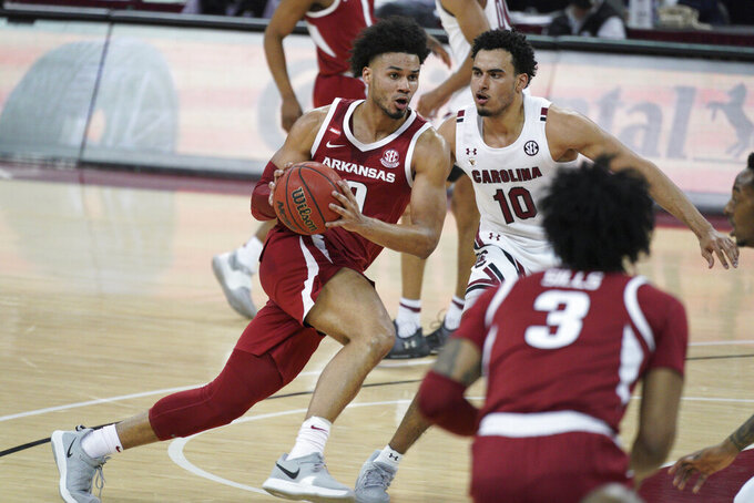 Arkansas forward Justin Smith (0) drives against South Carolina forward Justin Minaya (10) during the second half of an NCAA college basketball game Tuesday, March 2, 2021, in Columbia, S.C. (AP Photo/Sean Rayford)