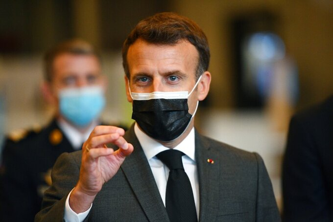 French President Emmanuel Macron talks to the press as he visits a giant vaccination center against the Covid-19 during its inauguration at Porte de Versailles convention centre in Paris, Thursday, May 6, 2021. (Christophe Archambault, Pool Photo via AP)