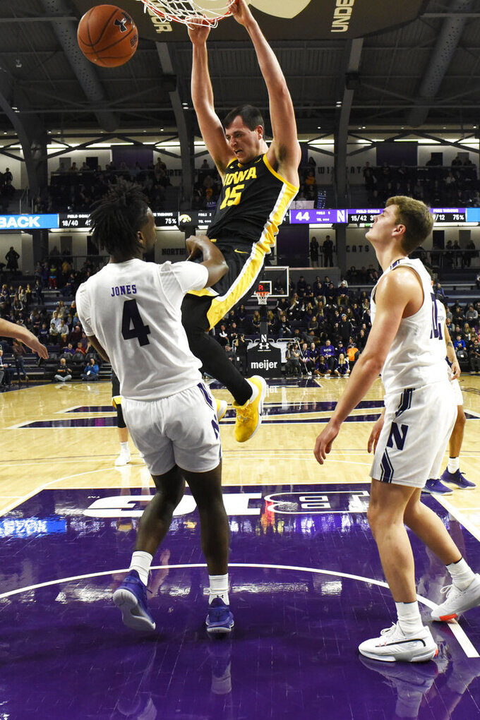 Iowa forward Ryan Kriener (15) dunks above Northwestern forward Jared Jones (4) during the second half of an NCAA college basketball game Tuesday, Jan. 14, 2020, in Evanston, Ill. (AP Photo/David Banks)