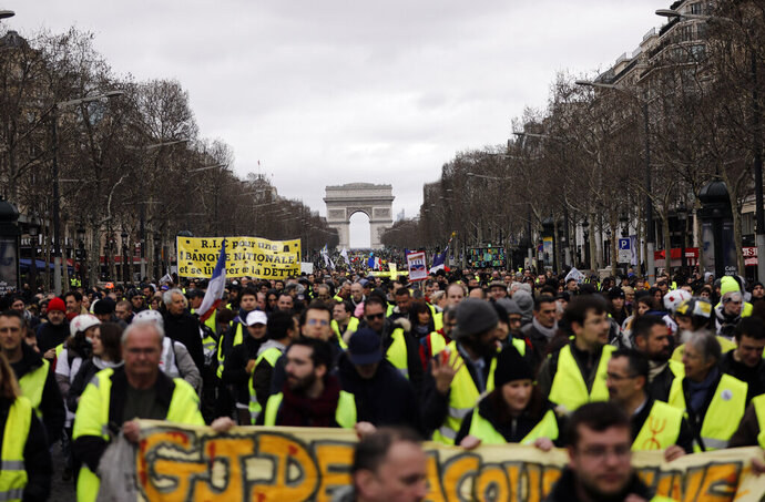 FILE - In this March 2, 2019 file photo, Yellow Vests protesters march on the Champs Elysees avenue in Paris. France's yellow vest protesters remain a force to be reckoned with five months after their movement started, and as President Emmanuel Macron announces his responses to their grievances. It includes people across political, regional, social and generational divides angry at economic injustice and the way President Emmanuel Macron is running France. (AP Photo/Kamil Zihnioglu, File)