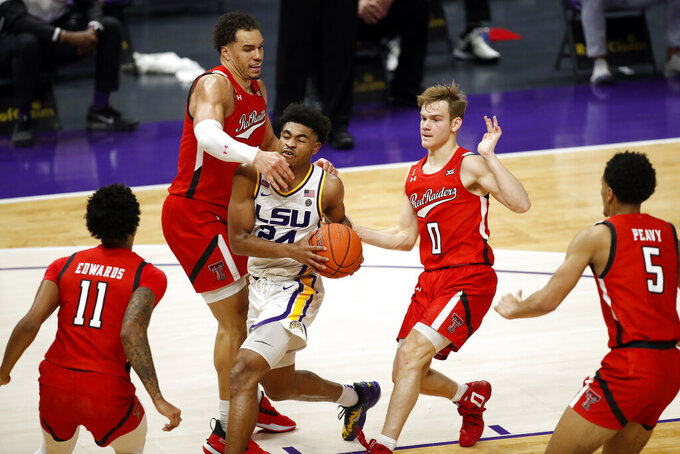 LSU guard Cameron Thomas (24) drives between Texas Tech forward Marcus Santos-Silva (14) and guard Mac McClung (0) in the second half of an NCAA college basketball game in Baton Rouge, Saturday, Jan. 30, 2021. Texas Tech won 76-71. (AP Photo/Tyler Kaufman)