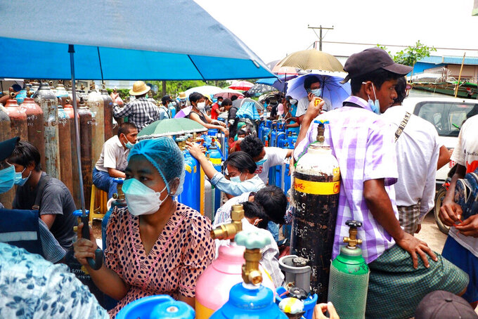 People wait in line next to oxygen tanks to be refilled outside the Naing oxygen factory at the South Dagon industrial zone in Yangon, Myanmar, Wednesday, July 28, 2021. Myanmar is currently reeling from soaring numbers of COVID-19 cases and deaths that are badly straining the country's medical infrastructure. (AP Photo)