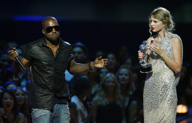 FILE - In this Sept. 13, 2009 file photo, singer Kanye West takes the microphone from singer Taylor Swift as she accepts the