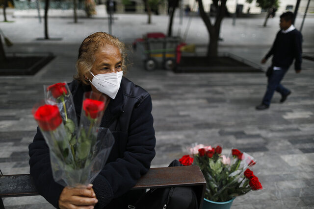 Wearing a mask to curb the spread of the new coronavirus, Martha Gonzalez Reyes, 76, sells roses outside Metro Hidalgo in central Mexico City, Monday, Aug. 10, 2020. After four months staying at home, Gonzalez returned to selling on August 1, but she says business hasn't fully rebounded.