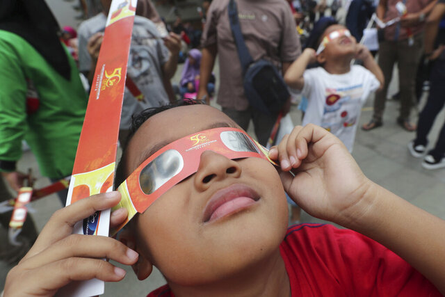 A kid looks up at the sun wearing protective glasses to watch a solar eclipse from Jakarta, Indonesia, Thursday, Dec. 26, 2019. (AP Photo/Tatan Syuflana)