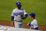 Los Angeles Dodgers' Mookie Betts (50) gets a high-five from manager Joe Maddon, right, after scoring off of a line drive hit by Justin Turner during the fifth inning of a baseball game Saturday, May 8, 2021, in Anaheim, Calif. (AP Photo/Ashley Landis)