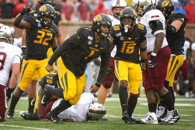 FILE - In this Oct. 5, 2019, file photo, Missouri defensive lineman Jordan Elliott, center, celebrates after tackling Troy quarterback Kaleb Barker, bottom, during the first half of an NCAA college football game, in Columbia, Mo. Elliott was selected to The Associated Press All-Southeastern Conference football team, Monday, Dec. 9, 2019.(AP Photo/L.G. Patterson, File)