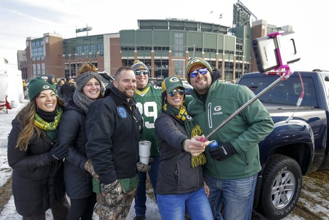 Fans take a selfie as they tailgate before an NFL football game between the Green Bay Packers and the Washington Redskins Sunday, Dec. 8, 2019, in Green Bay, Wis. (AP Photo/Mike Roemer)