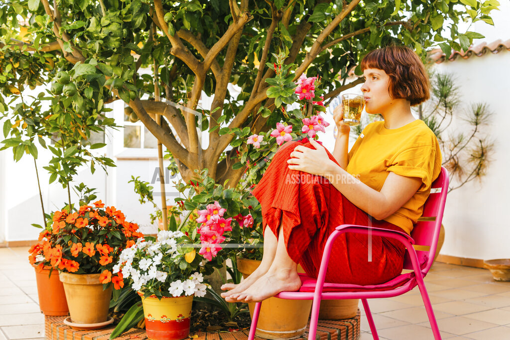 Woman drinking tea while looking away in home garden