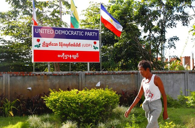 A man walks in front of a billboard of the United Democratic Party outside the party's headquarters Wednesday, Sept. 30, 2020, in Naypyitaw, Myanmar. Kyaw Myint, the chairman of the United Democratic Party, has been arrested as a fugitive from justice after recent reports in Myanmar media contained allegations of a shady past, including financial finagling and a prison escape. The party is fielding the second highest number of candidates for the November elections, and other party executives say it will carry on campaigning. (AP Photo/Aung Shine Oo)