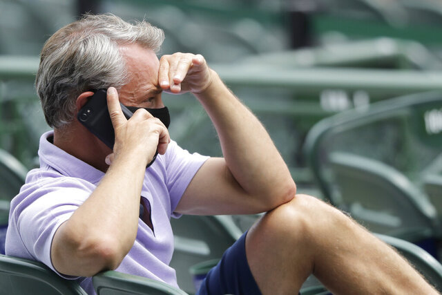 FILE - Chicago Cubs general manager Jed Hoyer talks on the phone as he watches players during the baseball team's practice at Wrigley Field in Chicago, in this Wednesday, July 8, 2020, file photo. Hoyer insisted the Chicago Cubs are taking a different approach this time. They plan to remain competitive while they retool rather than bring out the wrecking ball the way they did nine years ago. (AP Photo/Nam Y. Huh, File)