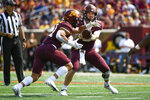 Minnesota quarterback Tanner Morgan hands off to running back Bryce Williams during the first half of an NCAA college football game against against Miami of Ohio Saturday, Sept. 11, 2021, in Minneapolis. Minnesota won 31-26. (AP Photo/Craig Lassig)