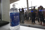 A large bottle of hand sanitizer sits next to a door as fans prepare to enter the arena for an NBA basketball game between the San Antonio Spurs and the Dallas Mavericks in San Antonio, Tuesday, March 10, 2020. (AP Photo/Eric Gay)