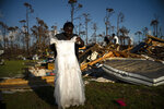 In this Sept. 8, 2019 photo, Synobia Reckley holds up the dress her niece wore as a flower girl at her wedding, as she goes through valuables in the rubble of her home destroyed one week ago by Hurricane Dorian in Rocky Creek East End, Grand Bahama, Bahamas. Synobia, 25, married two days after Hurricane Mathew in 2016, which passed over her home without doing serious damage. (AP Photo/Ramon Espinosa)