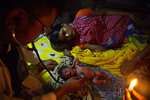 In this Friday, July 19, 2019 photo, Community health officer Parag Jyoti Das examines a newborn baby girl, as the infant's mother Imrana Khatoon, 20, lies by her side inside their flood affected home in Gagalmari, east of Gauhati, India. Khatoon delivered her first baby on a boat in floodwaters early Friday while on her way to a hospital, locals said. The woman and the newborn were brought back to their home without getting to hospital. They were however moved to a hospital on a boat to the nearby Jhargaon town because of unhygienic conditions due to floodwaters, Das said. (AP Photo/Anupam Nath)