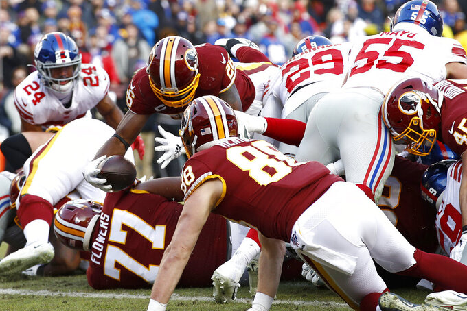 Washington Redskins running back Adrian Peterson (26) dives over a scrum while scoring a touchdown against the New York Giants during the second half of an NFL football game, Sunday, Dec. 22, 2019, in Landover, Md. (AP Photo/Patrick Semansky)
