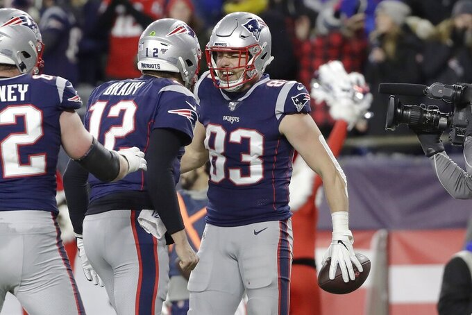 New England Patriots quarterback Tom Brady, left, celebrates his touchdown pass to tight end Matt LaCosse, right, in the first half of an NFL football game against the Buffalo Bills, Saturday, Dec. 21, 2019, in Foxborough, Mass. Brady[s touchdown pass was the 539th of his career, tying Peyton Manning for second all-time most touchdown passes by an NFL quarterback. (AP Photo/Elise Amendola)
